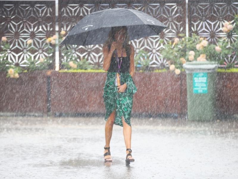 A racegoer holds an umbrella in the heavy rain